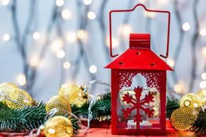 Eine Rote Weihnachtslanterne mit Tannenzweigen und Lichtern