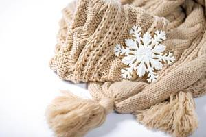 Eine Schneeflocke auf beigem gestricktem Schal