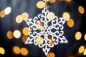 Eine schöne Schneeflocke vor mit funkelnden Lichtern dunklem Hintergrund