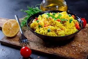Eine Schüssel Curryreis mit Gemüse auf einem alten Küchenbrett mit Olivenöl, Tomate und Kräutern