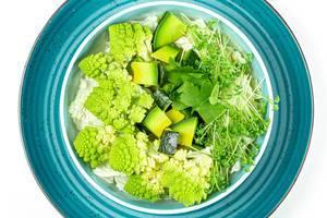 Eine Schüssel mit frischem Salat, Romanesco Kohl, Avocado, Petersilie und Wasserkresse auf einem Teller von oben fotografiert