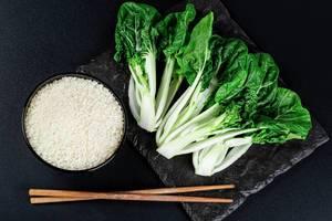 Eine Schüssel Reis, Essstäbchen und Pak Choi auf einem Brett vor schwarzem Hintergrund, Aufnahme von oben