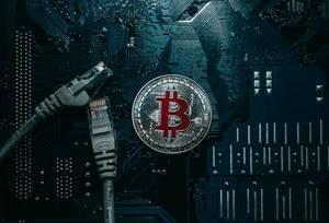Eine silberne Bitcoin-Münze und ein Netzwerk-Kabel auf einer Computerplatine
