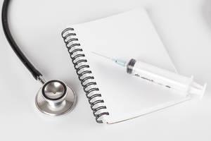 Eine Spritze liegt auf einem leeren Notizbuch neben einem Stethoskop Draufsicht