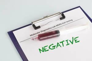 Eine Spritze mit Blutprobe liegt auf einem negativem MERS CoV Test auf weißem Hintergrund