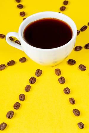 Eine Tasse-frischer Kaffee auf gelbem Hintergrund mit Kaffeebohnen