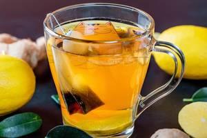Eine Tasse grüner Tee mit Zitronen und Ingwer - Nahaufnahme