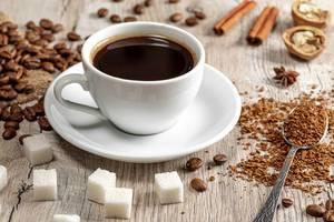 Eine Tasse heißer Kaffee mit ganzen und gemahlenen Kaffeebohnen, Zucker und Gewürzen auf einem Holzhintergrund