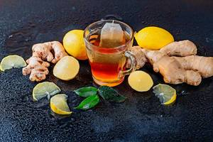 Eine Tasse heißer Tee mit Ingwer und Zitrone mit grünen Teeblättern, Ingwerwurzeln und Zitronen auf schwarzem Hintergrund