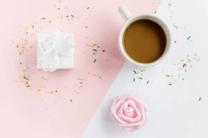 Eine Tasse Kaffee, Geschenkbox und bunte Streusel von oben fotografiert