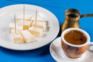 Eine Tasse Kaffee mit türkischer Kupfer-Karaffe und Lokum, Turkish Delight, auf einem blauen Holztisch