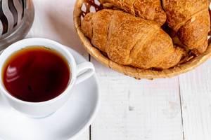 Eine Tasse Tee mit Croissants in einem Korb