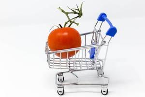 Eine Tomate in einem kleinen Einkaufswagen