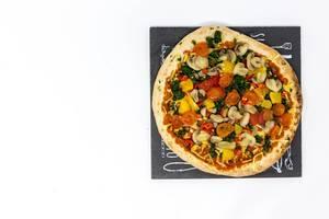 Eine vegane Pizza mit Champignons, Spinat, Paprika und Tomaten auf einem Schild - Aufsicht