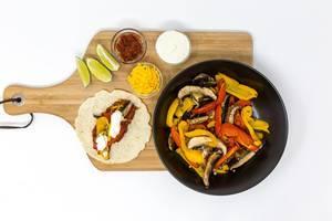 Eine vegetarische Fajita mit Paprika und Pilzen, scharfer Tomatensoße, Cheddar-Käse und Schmand mit Limettensaft mit dem Zutaten auf einem Brettchen auf weißem Hintergrund in der Aufsicht