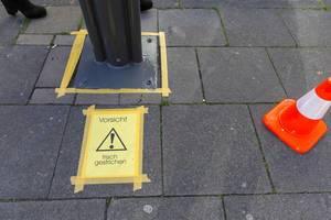 Eine Warnung vor frisch gestrichenen Pfeiler auf Bürgersteig mit Warnhütchen