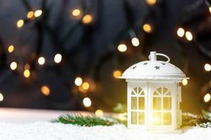Eine  weiße Weihnachtslanterne mit leuchtender Kerze im Schnee vor Lichtern im Hintergrund