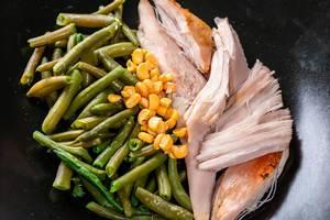 Einfaches Mittagessen mit Hühnerfilet, Spargelbohnen und Mais in einer schwarzen Schale