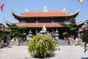 Eingang eines buddhistischen Tempel mit asiatischen Schriftzeichen und Bepflanzung