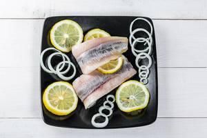 Eingelegter Hering mit Zitrone und Zwiebel auf einem schwarzen Teller