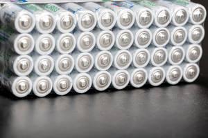 Eingeschweißte AAA Alkaline-Batterien auf einem schwarzen Tisch Nahaufnahme