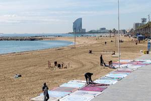 Einheimische Straßenhändler verkaufen Teppiche am Platja del Somorrostro Sandstrand vor dem Mittelmeer in Barcelona, Spanien