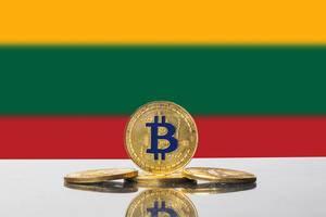 Einige goldene Bitcoins vor der Staatsflagge Litauens