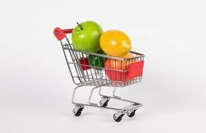Einkaufswagen gefüllt mit frischen Früchten wie Apfel und Zitrone vor weißem Hintergrund