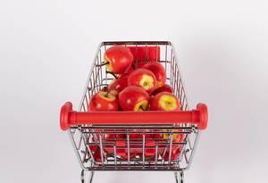 Einkaufswagen gefüllt mit süßen roten Äpfeln vor weißem Hintergrund