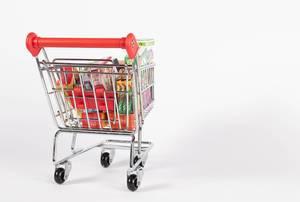 Einkaufswagen gefüllt mit verschiedenen Produkten und Nahrungsmitteln vor weißem Hintergrund