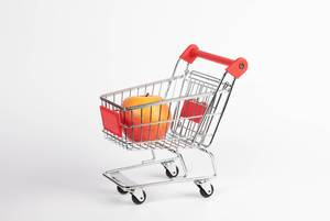 Einkaufswagen mit frischem, knackigem Apfel vor weißem Hintergrund