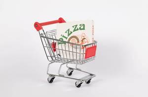 Einkaufswagen mit Pizzakarton von Lieferdienst vor weißem Hintergrund