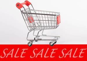Einkaufswagen mit Schriftzug SALE (Schlussverkauf) vor rotem und weißem Hintergrund