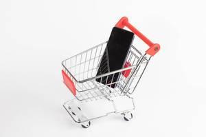 Einkaufswagen mit schwarzem Mobiltelefon vor weißem Hintergrund