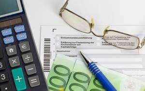 Einkommenssteuererklärung mit einem Taschenrechner, Geld, einer Brille und einem Stift