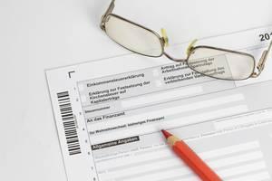 Einkommenssteuererklärung mit Brille und einem Buntstift