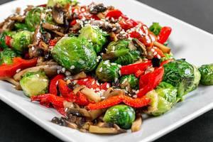 Eintopf mit Gemüse und Pilzen, Sesam und roter Paprika in der Nahaufnahme