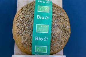 Einzelnes rundes Bio-Brot mit Sonnenblumenkernen und Bio-Siegel der EU