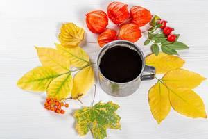 Eiserne Tasse gefüllt mit Kaffee und umrandet von herbstlichen und bunten Blättern