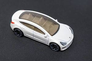 Electric car as a toy;: Hot Wheels Tesla Model 3 with glass roof, on dark surface