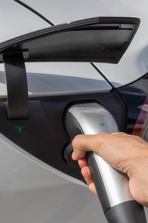 Electric vehicle: Man holding a type 2 connector during Tesla charging in Wilnsdorf, Germany