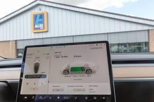Electromobility: Tesla Model 3 touch-screen display shows current charging status and battery status, while charging the E-Car at a German Aldi-parking lot
