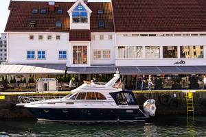 Elegant yacht in the harbor of Bergen, Norway with restaurant Olivia Zachariasbryggen behind (Flip 2019)