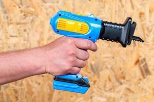 Elektrische Säge als Plastikspielzeug, in einer Männerhand