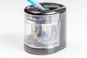 Elektrische Spitzmaschine: blauer Buntstift vor einem Anspitzer mit weißem Hintergrund