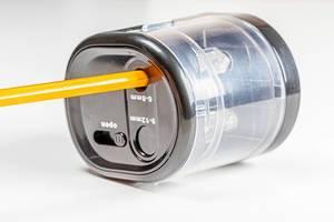 Elektrischer Bleistiftanspitzer mit orangem Buntstift vor weißem Hintergrund