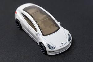 Elektroauto als Spielzeug;: Hot Wheels Tesla mit Glasdach, auf dunkler Oberfläche