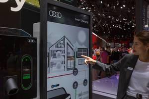 Elektroauto und Smart Home vernetzen: Frau zeigt auf das Home Energy Management System von Audo Smart Charging Ladesystem