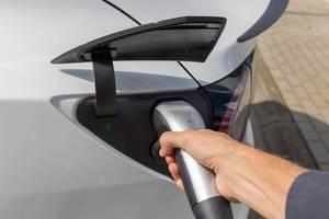 Elektrofahrzeug: Mann hält einen Typ-2 Stecker während der Tesla-Aufladung