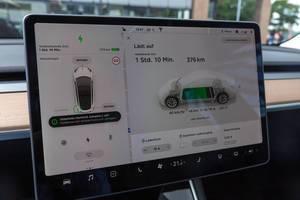 Elektromobilität: Touchscreen-Display im Tesla Model 3 zeigt den aktuellen Ladevorgang und Batteriestatus an